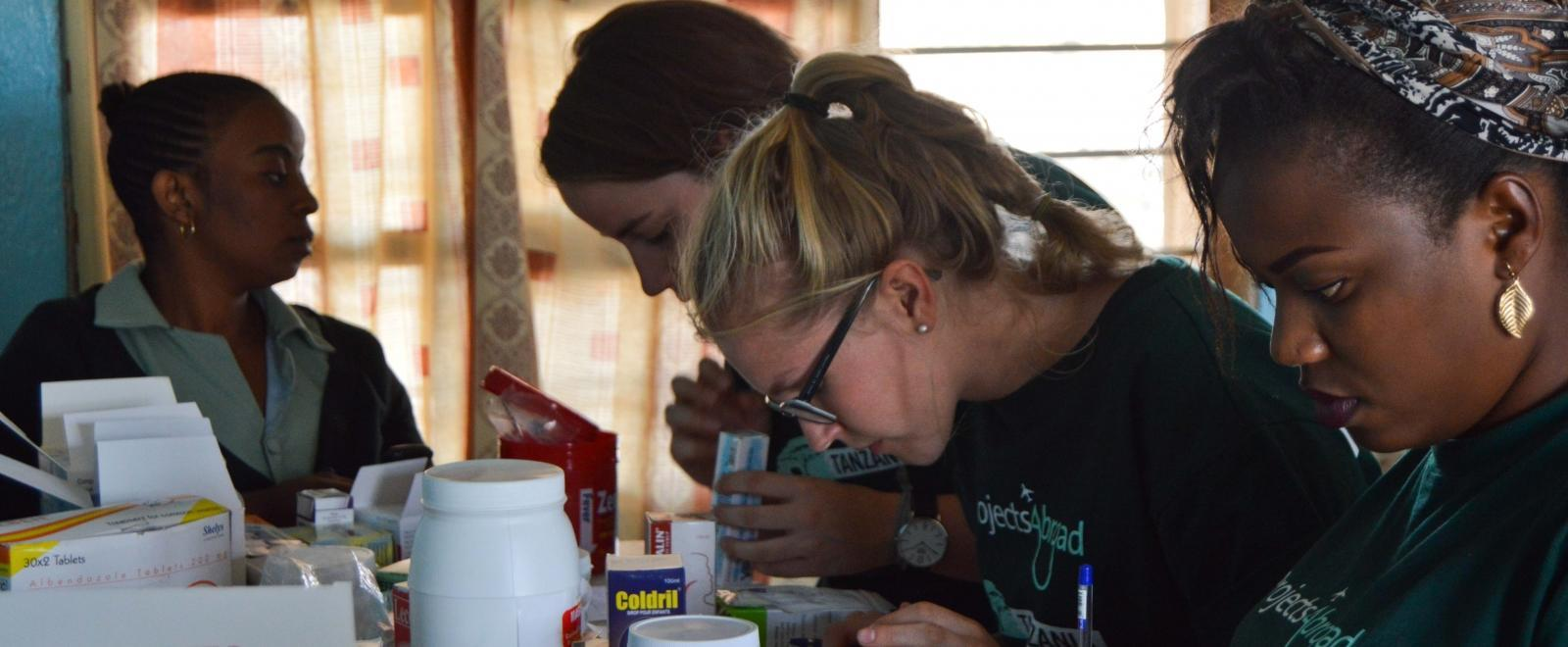 Pharmacy interns in Tanzania sort and label medication needed for a medical outreach.